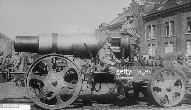 Austrian Army sits astride a large mobile artillery siege gun; they are uniformed and bear rifles as they hover around and on the wheeled cart during...