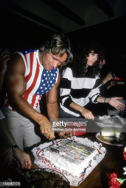 Austrian Bodybuilder and actor Arnold Schwarzenegger cuts the cake at a party to celerate his becoming a US citizen on September 17 1983 in Los...