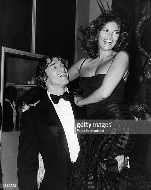 Austrian bodybuilder and actor Arnold Schwarzenegger holds American actor Raquel Welch in the air at the Golden Globe Awards Beverly Hilton Hotel...