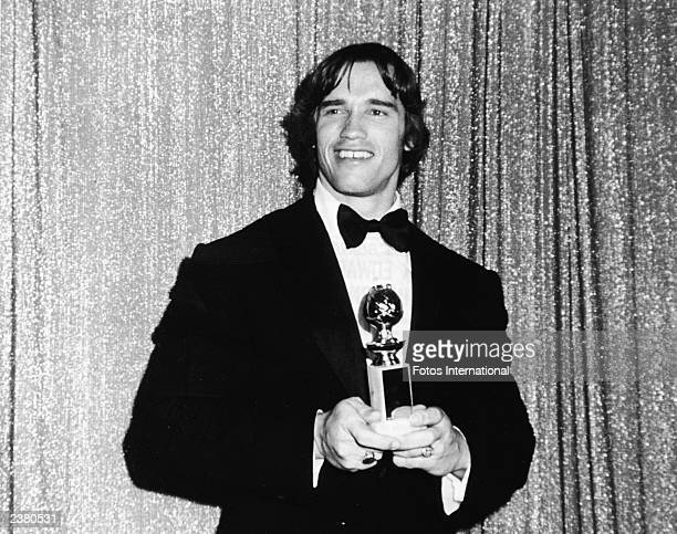 Austrian bodybuilder and actor Arnold Schwarzenegger posing with his award for Most Promising Newcomer to Films for the film Stay Hungry at the...