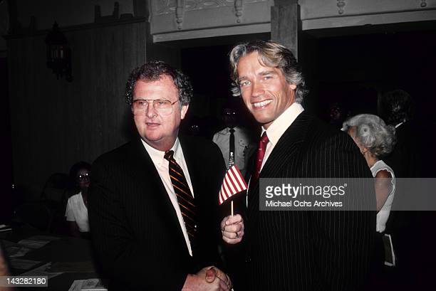 Austrian Bodybuilder and actor Arnold Schwarzenegger shakes hands with Immigration Official Harold W Ezell after becoming a US citizen on September...