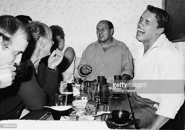 Austrian bodybuilder Arnold Schwarzenegger laughs while eating dinner with a group of people after winning the Mr Universe contest London England...