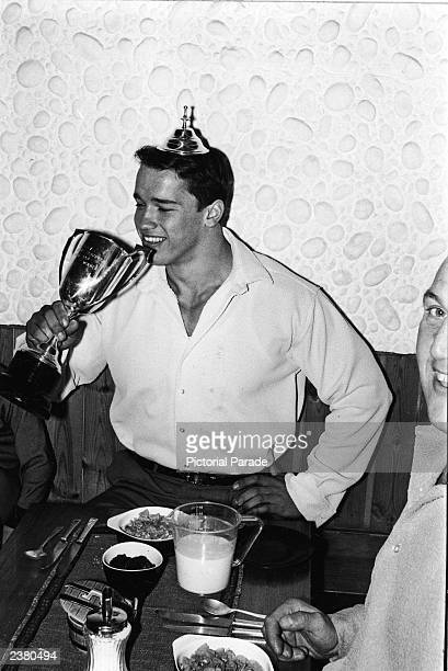 Austrian bodybuilder Arnold Schwarzenegger pretends to drink from his trophy while wearing its lid as a crown after winning the Mr Universe contest...