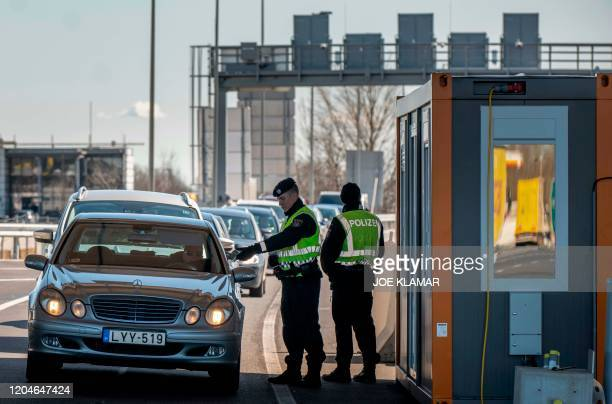 Austrian border policemen check papers of car passenger at the AustroHungarian border in Nickelsdorf Austria near Hegyeshalom Hungary on March 22020...