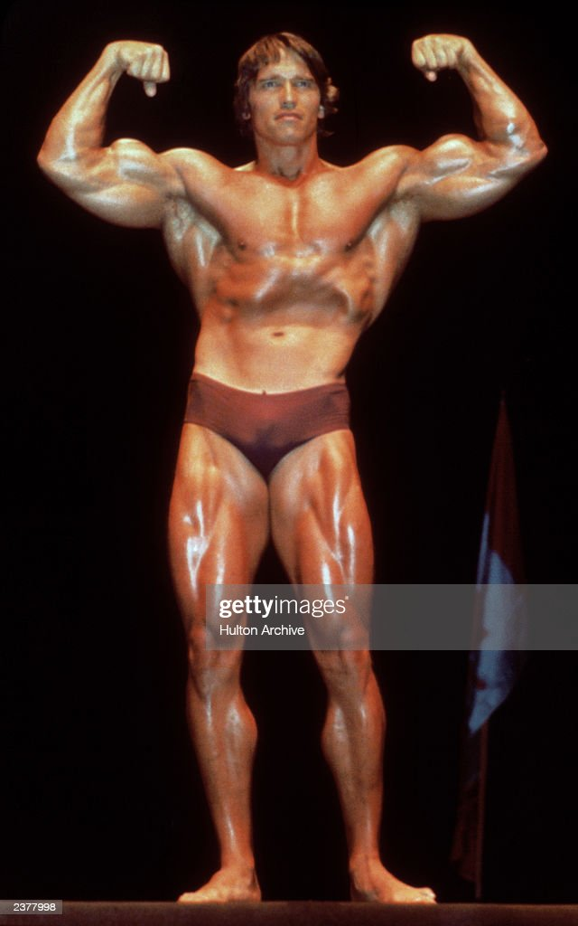 Austrian Born Actor And Former Bodybuilder Arnold Schwarzenegger Poses In A  Bathing Suit And Flexes His