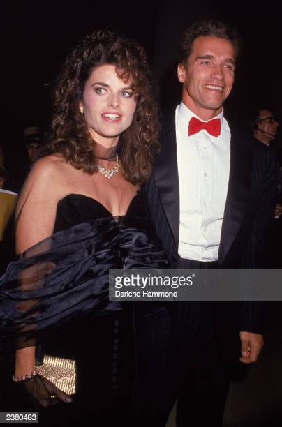 Austrian born actor Arnold Schwarzenegger and wife Maria Shriver stand dressed in formal wear at an event, circa 1986.