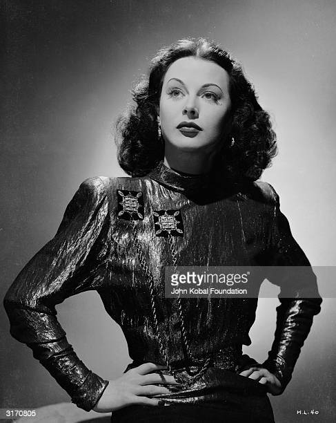 Austrian born actress Hedy Lamarr stands with her hands on her hips wearing a shimmering blouse decorated with cord She is starring as Irene in 'The...