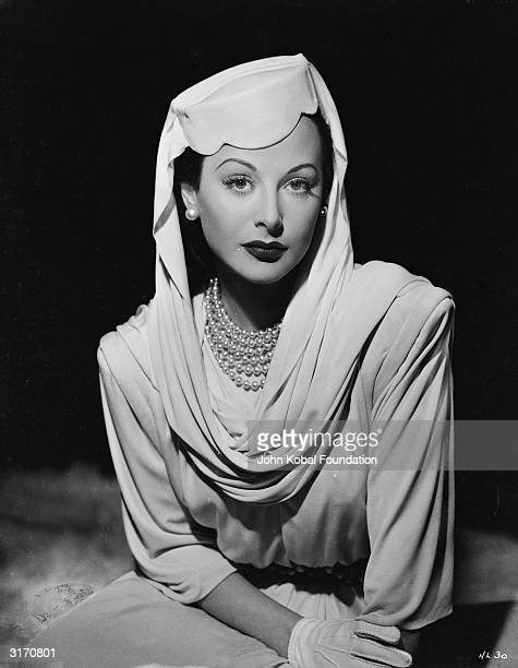 Austrian born actress Hedy Lamarr wearing a pearl necklace and matching earrings with a pill box hat and draped scarf She is starring as Irene in...