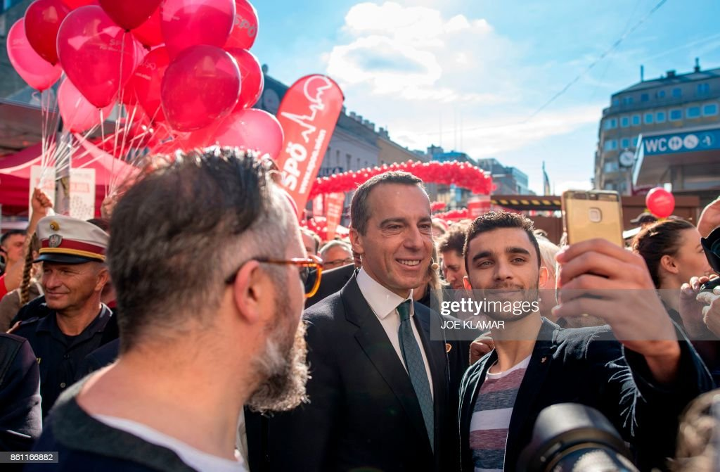 TOPSHOT - Austrian Chancellor and leader of the Social Democrats (SPOe) Christian Kern (C) poses for a selfie with supporters during the last election rally on the eve of the Austrian parliamentary elections on October 14, 2017 in Vienna, Austria. Austria holds snap general elections on Sunday, October 15, 2017. /