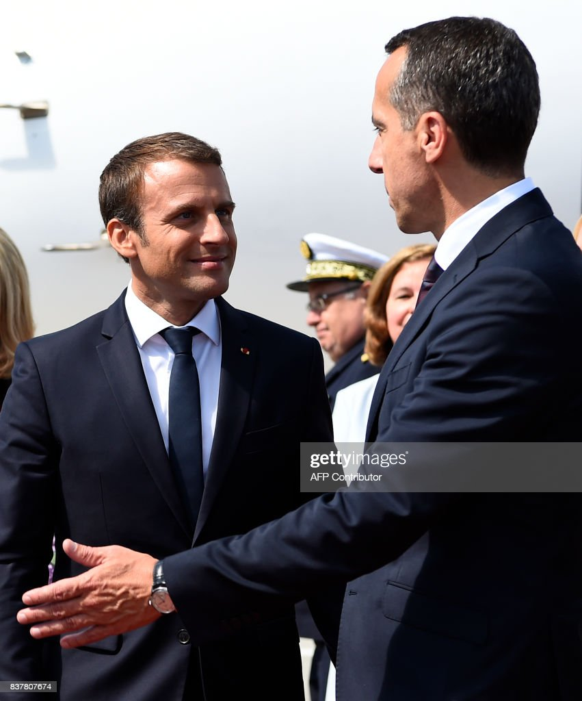 Austrian chancellor Christian Kern (R) welcomes French President Emmanuel Macron upon arrival on August 23, 2017 at the airport in Salzburg. / AFP PHOTO / AFP PHOTO AND POOL / Bertrand GUAY