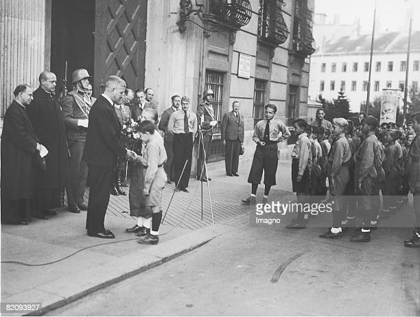 Austrian chancellor Kurt Schuschnigg at the Michaelerplatz in Vienna A group of young adults of the Reichsbund is honoring him Photograph Around 1930...