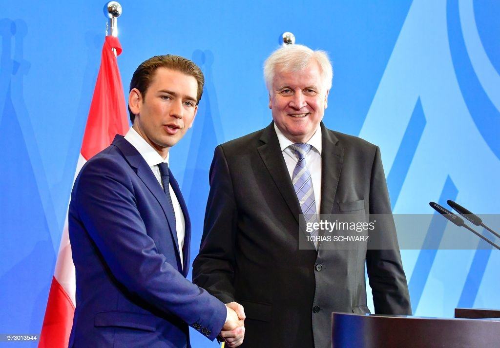 Austrian Chancellor Sebastian Kurz (L) shake hands German Interior Minister Horst Seehofer speaks after a press conference at the Interior Ministry in Berlin, on June 13, 2018.