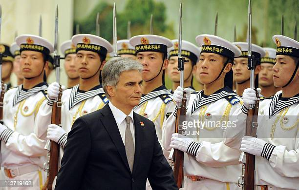 Austrian Chancellor Werner Faymann reviews a Chinese military honour guard during a welcoming ceremony at the Great Hall of the People in Beijing on...
