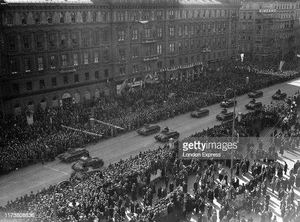 Austrian citizens give the Nazi salute as German Wehrmacht Panzerkampfwagen I PzKpfw I tank's parade through the streets of Vienna past the Cafe...