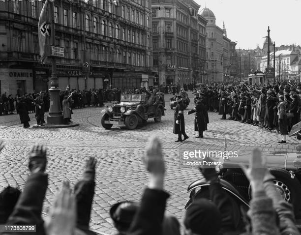 Austrian citizens give the Nazi salute as German Wehrmacht troops and artillery parade through the streets of Vienna after the German Fuhrer and...