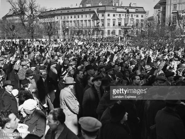 Austrian citizens give the Nazi salute at the Hofburg in Vienna after the German Fuhrer and Chancellor Adolf Hitler had entered the city proclaiming...