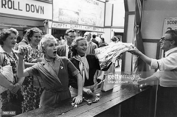 Austrian coloratura soprano Josette Adrienne appearing at the Grand Theatre Brighton spends some free time playing darts on a fairground stall on the...