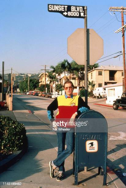 """Austrian Film actor Helmut Berger, star of TV series """"Dynasty"""" leans on mailbox along Sunset Boulevard in Los Angeles, California circa 1985;"""