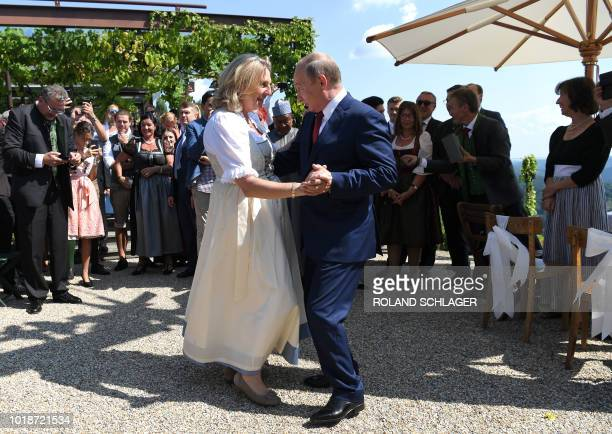 TOPSHOT Austrian Foreign Minister Karin Kneissl and Russian President Vladimir Putin dance during her wedding on August 18 2018 in Gamlitz Styria...