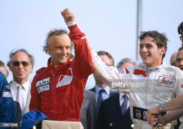 Austrian Formula One racing driver Niki Lauda raises the hand of 3rd placed driver Ayrton Senna on the podium after driving the Marlboro McLaren...