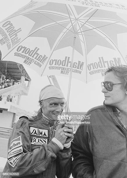 Austrian Formula One racing driver Niki Lauda shelters from the rain with McLaren director Mansour Ojjeh under a Marlboro branded umbrella during...