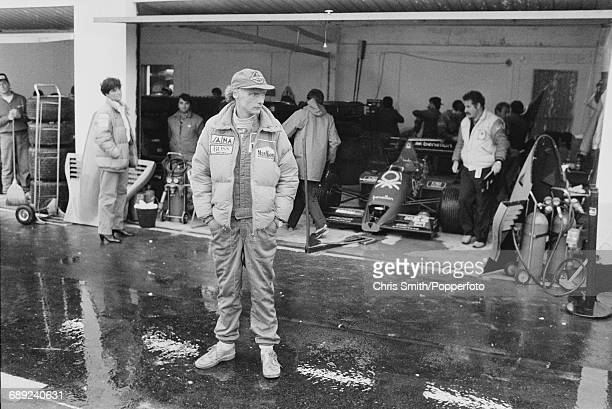 Austrian Formula One racing driver Niki Lauda stands outside the Benetton Alfa Romeo pit garage during qualifying for the 1984 Portuguese Grand Prix...
