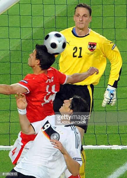 Austrian goalkeeper Jurgen Macho watches Austrian defender Gyorgy Garics jump for a header next to German forward Mario Gomez during the Euro 2008...