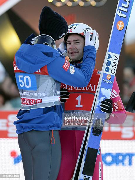 Austrian Gregor Schlierenzauer congratulates the winner Norwegian Anders Jacobsen after the second competition jump of the FourHills Ski jumping...