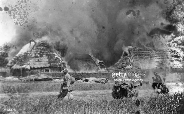 Austrian Infantry passing through a burnt-out village.