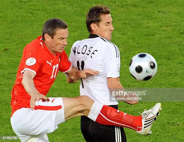 Austrian midfielder Umit Korkmaz vies with German forward Miroslav Klose during the Euro 2008 Championships Group B football match Austria vs....
