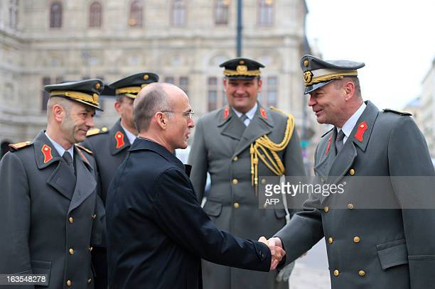 Austrian Minister of Defence Gerald Klug shakes hands with an officer of the Austrian army prior to the commemoration ceremony of the 75th...
