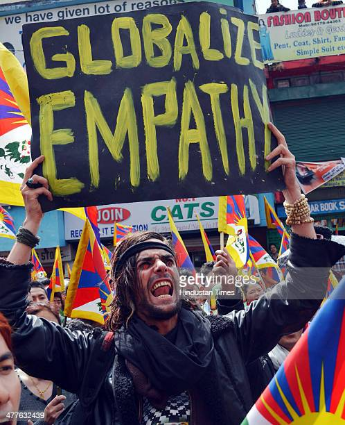 Austrian national Maximilian with a Tibetan flag attached to his hat joins exiled Tibetans at a gathering to mark the 55th anniversary of the failed...