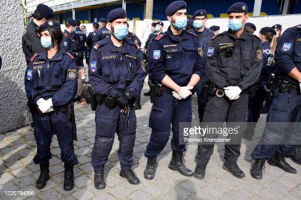 Austrian police wearing face masks arrest a man during a demonstration against the government measures to slow down the spread of coronvirus on April...