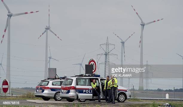 Austrian policemen blockes the motorway A4 near the AustrianHungarian border near Austrian village of Nickelsdorf on September 5 2015 from where...