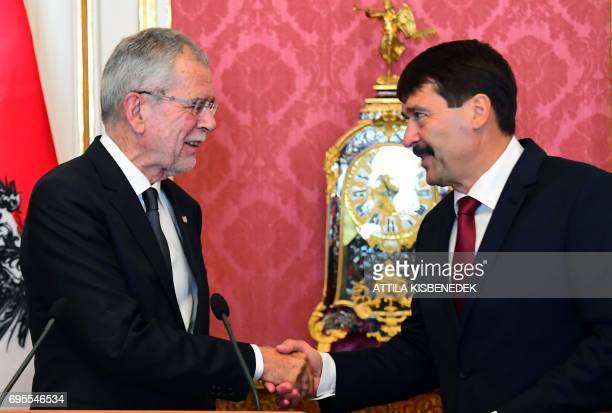 Austrian President Alexander van der Bellen shakes hands with his Hungarian counterpart Janos Ader at the Maria Theresia Hall of the presidential...
