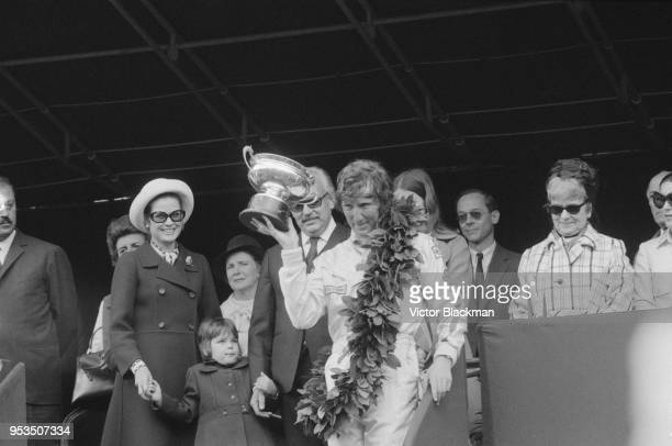 Austrian racing driver Jochen Rindt wins 1970 Monaco Grand Prix and holds his trophy in the presence of Rainier III, Prince of Monaco and Princess of...