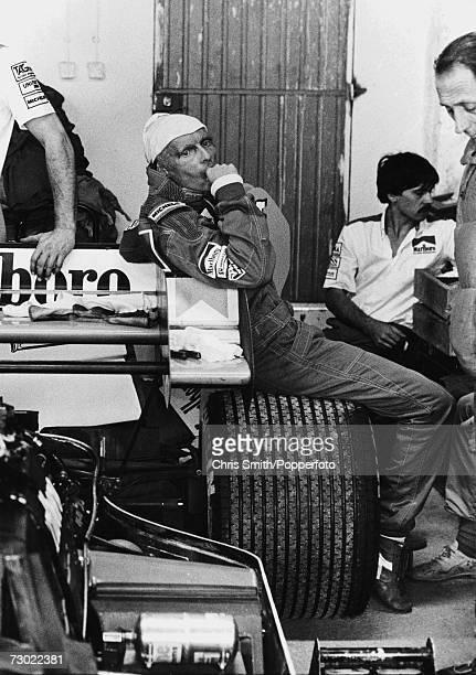 Austrian racing driver Niki Lauda sitting on the rear wheel of his Marlboro McLaren circa 1984