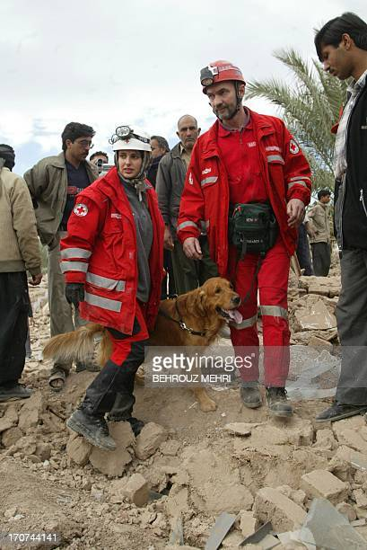 Austrian Red Cross rescue workers detect the rubble for survivors with their sniff dog at the devastated southeastern Iranian city of Bam 28 December...