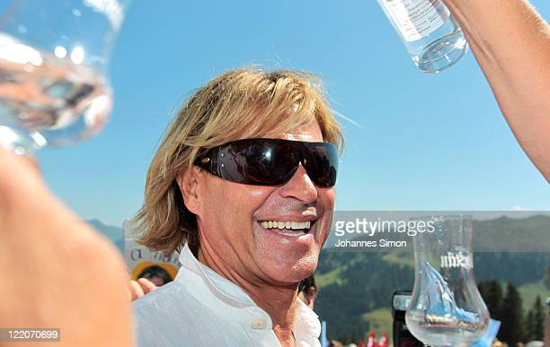Austrian singer Hansi Hinterseer drinks liqueur during his annual fan hiking tour beginning at the peak of the Hahnenkamm mountain on August 25, 2011...