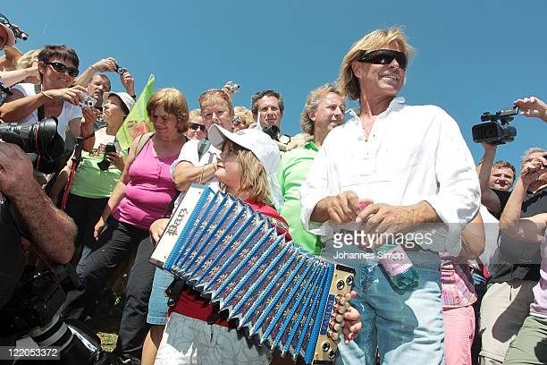Austrian singer Hansi Hinterseer listens to a young accordeon and is surrounded by fans player during his annual fan hiking tour beginning at the...