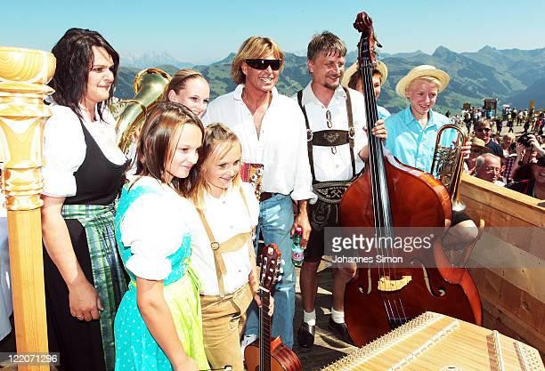 Austrian singer Hansi Hinterseer poses wth Tyrolian folk musician during his annual fan hiking tour beginning at the peak of the Hahnenkamm mountain...