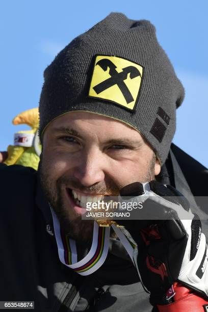 CORRECTION Austrian snowboarder Andreas Prommegger celebrates on the podium after winning the men's Parallel Slalom PSL in the FIS Snowboard and...