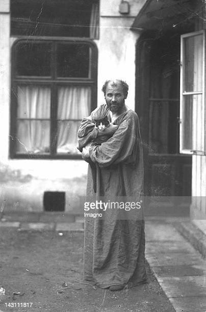 Austrian symbolist painter Gustav Klimt holding one of his cats in his arms in front of his studio at Josefstaedter Strasse 21 Vienna Austria