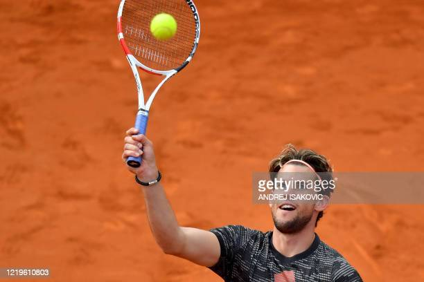 Austrian tennis player Dominic Thiem returns the ball during an exhibition double match at a charity exhibition hosted by Novak Djokovic on June 12...