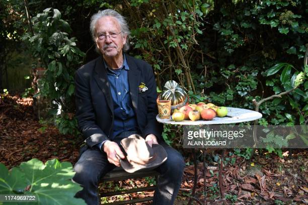 Austrian writer Peter Handke poses in his garden in Chaville in the Paris surburbs on October 10 2019 after he was awarded with the 2019 Nobel...