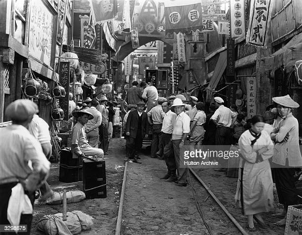 AustrianAmerican director Josef von Sternberg stands in a recreation of a typical Chinese street with a group of extras as he prepares a shot for the...
