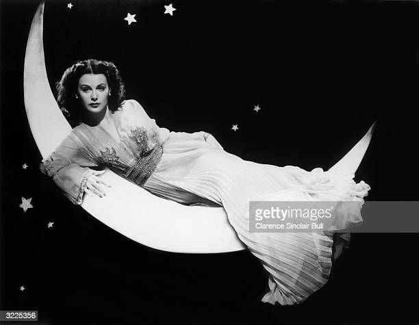 Austrian-born actor Hedy Lamarr reclining on a crescent moon in front of a starry night-time backdrop, in a promotional portrait from director...
