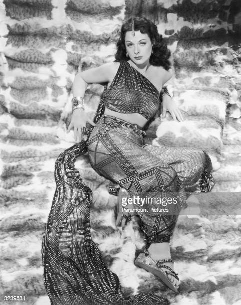 Austrianborn actor Hedy Lamarr wearing a haremstyle costume reclines on a fur backdrop in a fulllength promotional portrait for director Cecil B...