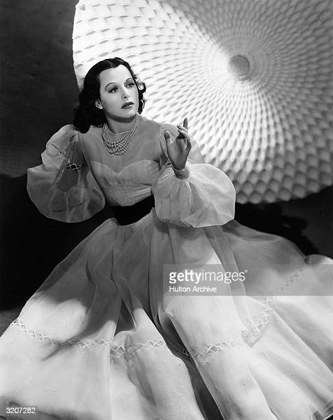 Austrianborn actor Hedy Lamarr wears a lightcolored taffeta gown and gestures in front of a large circular tissue paper prop in a promotional...