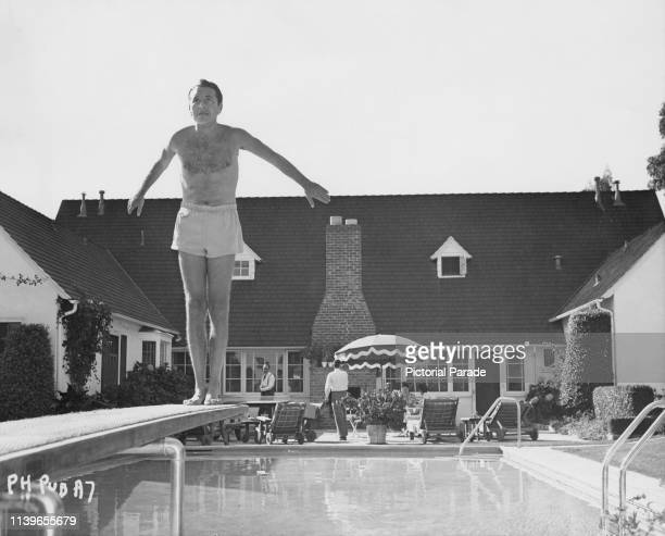 Austrianborn American actor Paul Henreid looks nervous as he prepares to do a backward dive from a diving board circa 1950